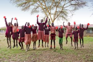 Kenya, Narok District, Narok. February 16, 2010 WFP Beneficiaries of the School Meals Programme jump together in a group shot with their red cups in hand, outisde the Enkare Nairowua Primary School in Narok. Featured in the photo is Moses Kulale (1st on the left); Caroline Kool (sixth from the left); Mailogi Ikokia (third from the right); and Oltetia Sayialel (second from the right). The WFP's commitment to School Meals Programmes in Kenya is high: the programme is rooted in the policy framework and there is a strong cooperation between WFP and the Ministry of Education. WFP is providing school meals to nearly 1.2 million children in Kenya. These are the most vulnerable children living in arid and semi-arid lands, and urban slums, who will receive at least one nutritious meal a day through WFP. Among the poor, there is often not enough food at home, and most schools in developing countries lack canteens or cafeterias. School meals are a good way to channel vital nourishment to poor children. Having a full stomach also helps them to concentrate better on their lessons. In countries where school attendance is low, the promise of at least one nutritious meal each day boosts enrolment and promotes regular attendance. Parents are motivated to send their children to school instead of keeping them at home to work or care for siblings. In the poorest parts of the world, a school meal programme can double primary school enrolment in one year. Among the key beneficiaries are girls, who otherwise may never be given the opportunity to learn. In this school, each child brings one stick and a small can of water every day (both of which are collected on the way to school). The water will be used for the plants in the school garden and the stick will be delivered to the kitchen to serve as fuel to cook the school meal. Since stoves have been introduced, schools have been able to save up to fifty percent of their fuel requirements and hence the method adopted in this